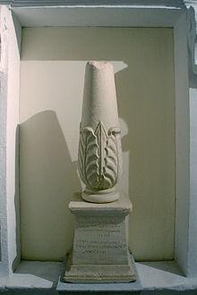 Photographie représentant un cippe, petite colonne tronquée en haut, renflée à la base et décorée d'un motif de feuillage. Elle repose sur un socle trapézoïdal dont la face avant porte les inscriptions - en phénicien au-dessus, en grec en-dessous.