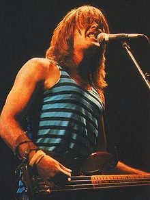 A fifty-eight year old man is singing into a microphone while playing a bass guitar. Behind him are stage lights and a partial view of a large steam train. His long white hair partly obscures his face. He wears a dark tee-shirt and darker pants.