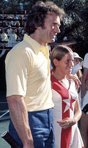 A man stands next to a girl as they both face to the left, smiling.