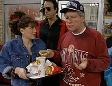 A man stands on the right dressed in a baseball cap and sweatshirt to resemble President Clinton. He is holding a burger which he has picked up from the women to his left's tray; several other products remain. A man in dark glasses stands behind them.