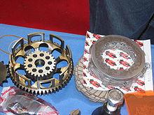 Les pièces d'un embrayage multidisque: à gauche, la cloche et la noix, à droite les disques