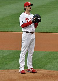A man in a white baseball uniform with red trim. He is wearing a red cap and holding his left hand behind a black baseball glove.