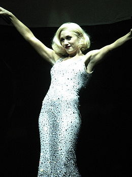 A blonde woman is standing with her arms up. She is wearing a long platinum dress that is adorned with jewellery. The background is black.