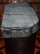 """""""Replica of the Rosetta Stone in the King&squot;s Library of the British Museum as it would have appeared to 19th century visitors, which was open to the air, held in a cradle that is at a slight angle from the horizontal and available to touch"""""""