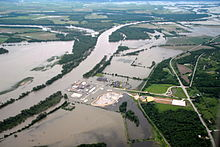 Aerial view of farms and a power station in a rural area partly inundated by a river that has overflowed its banks