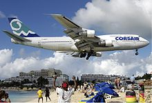 A Corsair 747-300 in white, blue and green livery during landing with its landing gear down, flying over a beach with people directly underneath.
