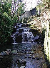 Photo d'une cascade avec en arrière-plan une bâtisse.