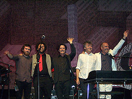 Five men are standing close together on a stage and smiling. First male at left is bearded and has right arm raised to shoulder height. Second male has arms around shoulders of his neighbours and is partly obscured by a microphone stand. Third male has left hand raised overhead. Fourth male has arms at side and is looking to his left. Fifth male has right arm over his neighbour and left arm overhead. Last two are partly obscured by a keyboard and its stand. Behind the five men is more band equipment and the background contains considerable English text.