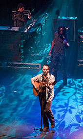 A man at the front of a stage holding a guitar and standing behind a microphone stand. Behind him are two men, one wearing sunglasses and holding a violin and the other in a striped shirt playing keyboards. The stage is lit from behind by a blue light that casts the shadows of leaves and thin branches.
