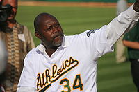 "A bald black male baseball player in his fifties pitches a baseball. He is wearing an white uniform with the word ""Athletics"" across it, and the number 34 below the lettering."