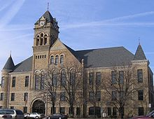 A large three-story stone building built in 1895. Three stories of windows line the front of the building with the two front corners containing cone-shaped roofs that stick out from the main roof. Above the entrance is a large clock tower that is taller than the rest of the building.