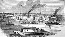 A black and white picture with boats on a river and buildings on the far side of the river