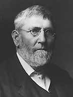 A middle-aged man with a beard and old-fashioned wire-framed glasses. His head and shoulders are visible, and he is turned three-quarters of the way towards the right. He is wearing a dark suit and waistcoat with a white shirt.
