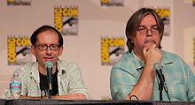 Two men sit at a table behind microphones, both have glasses, and one is shorter than the other.
