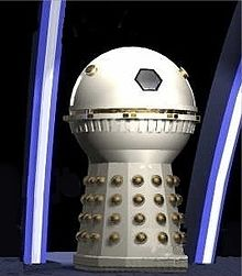 Image of a cream-coloured Dalek with a spherical head section and no appendages. The hemispheres and detailing around the dome midsection are painted in gold.