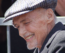 A smiling Dennis Hopper, appearing frail and aged, wearing a gray hat over his thin gray hair, with a bandage above his right eye.