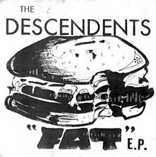 "A white album cover shows a pen-and-ink illustration of a cartoonish cheeseburger with a bite taken out of it. The band&squot;s name ""The Descendents"" is printed across the top in large, thin capital typeface. At the bottom is the title ""Fat"" in quotation marks in wide, black, hand-drawn capital letters, followed by ""E.P."" in thin, uneven typeface."