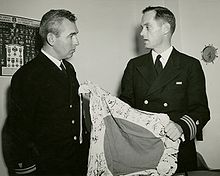 Two men in uniform, one holding a flag.