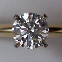 A clear faceted gem supported in four clamps attached to a wedding ring
