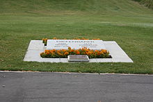 A grave marked by an angled slab of marble engraved with the names of Diefenbaker and his wife and surrounded by plantings of small marigolds, and an additional plaque in bronze. Beyond it a lawn stretches away.