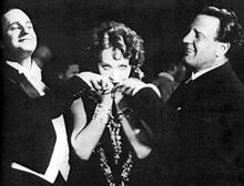 A woman, staring directly at camera, stands between two formally dressed, smiling men who gaze admiringly at her. Each is raising a hand, which she holds and kisses.