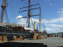 """Partial view of a ship moored to a quayside. Prominent visible features are a mast with three crossbeams, two smaller masts, a funnel, a lifeboat and rigging. Packing cases are lined up on the quay, and a gangplank with """"RRS Discovery"""" on it leads to the ship."""