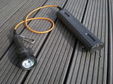 Two-part diving light with lamp assembly at left and battery pack at right, joined by a short cable