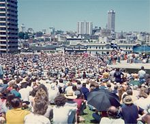 A large crowd has gathered in an open space in an urban setting (tall buildings are visible).  Far away can be seen a platform, and a banner reading SHAME FRASER SHAME.