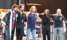 The five members of Dream Theater standing together in front of a drum kit and some amplifiers on a stage.
