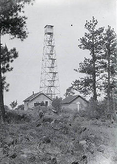 A four-legged tower with a small enclosure at the top, next to two one-story buildings. The tower is four stories tall. Trees are at either side, and in the foreground there are rocks, some vegetation, and a rough trail.