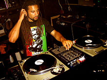 Man sitting in a studio before two turntables and audio turning buttons, adjusting the sound as he listens over earphones.