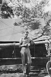 Whitlam in military uniform stands under a tree in front of a large tent.  He holds a mug in his hand.