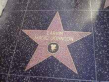 "A five-point star engraved on a tile. In the center of the star are the words ""EARVIN MAGIC JOHNSON"". An image of a movie camera is etched directly below these words, though still in the star."