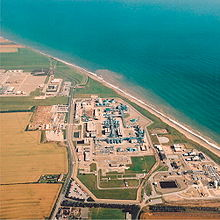 Aerial view of the gridiron arrangement of buildings and pipes beside the curving Yorkshire sea coast.