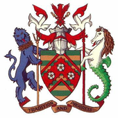 Blazon: Barry vert and Or on a chevron engrailed plain cotised gules three roses argent barbed and seeded proper. crest: issuing from a mural crown argent an eagle displayed gules armed and langued azure supporting with the dexter talons a sword hilt upwards and with the sinister talons a crozier in saltire Or; mantled gules doubled argent. Supporters: on the dexter a lion azure guardant armed and langued gules gorged with a wreath of barley supporting between the forelegs a trident Or; on the sinister a demi-horse argent langued gules maned Or the feet webbed vert conjoined to the lower half of a Hippocampus vert supporting between the forelegs set upon a staff a cross fleury gules.