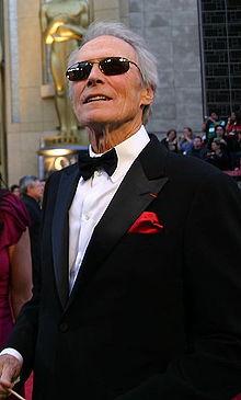 Clint Eastwood porte un costume noir avec une chemise blanche et un nœud papillon noir pour la cérémonie. On peut apercevoir en arrière plan la statue représentant les Oscars qui devance la salle de la cérémonie.