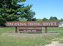 "Large wooden sign with ""Educational Testing Service"" in white letters, in the middle of a field overlooking several trees and a blue sky."
