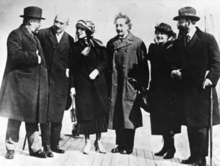 Casual group shot of four men and two women standing on a brick pavement.