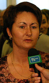 A woman with brown hair, speaking into a microphone.