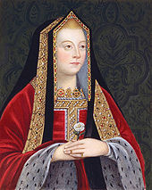 A blond woman with rosy cheeks holds a white rose. She wears a gilded black shawl over her head, and a red robe trimmed in white spotted fur.