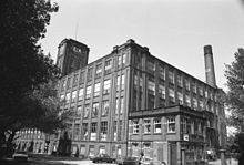A five-storey cuboid factory composed of brick and windows. The view is from the ground at one corner of the factory. To the right, appearing from behind the factory, is a tall brick chimney. To the left are trees appearing black, and at their fringe, a square brick tower connected to the factory.