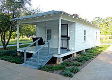 Present-day photograph of a whitewashed house, about 15 feet wide. Four bannistered steps in the foreground lead up to a roofed porch that holds a swing wide enough for two. The front of the house has a door and a single paned window. The visible side of the house, about 30 feet long, has two paned windows.