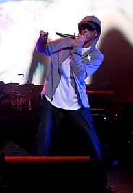 A man on a stage holding a microphone and wearing a hooded jacket, a white shirt, and blue jeans.