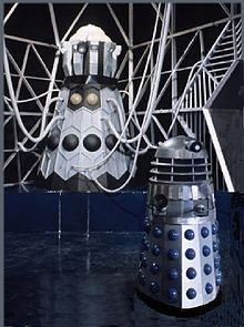 Image of the Dalek Emperor, standing upon a dark blue plinth, with a light grey geodesic framework in the background and a Mark 3 Dalek in the foreground.