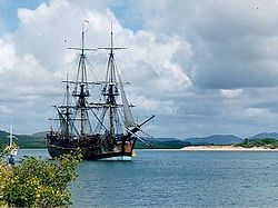 A three-masted sailing ship crossing a bay