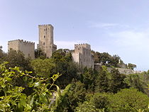 A castle with a tall narrow tower and walls topped by battlements stretches along the edge of a cliff covered in trees and palm trees.