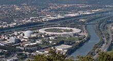 Confluent du Drac (arrière-plan) et de l'Isère (premier plan). Dans la presqu'île scientifique on voit les centres de recherche de l'Institut Laue-Langevin et du Synchrotron.  Vue depuis le Mont Jalla.