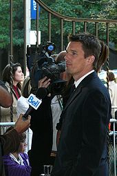 A Caucasian male with light brown hair wearing a black two-piece suit is being interviewed. A microphone is visible in the left foreground, and a television camera is visible in the background.