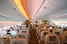 Cabina de Avión de pasajeros con dos pasillos. Cada asiento tiene un monitor; las luces brillan desde las paredes y los compartimientos de equipaje.