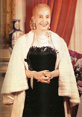 A picture of a Evita, former first lady of Argentina. Her hair is drawn into a tight bun at the back. She is wearing a black, low-cut dress. Around her neck is a number of chains. The lady's hands are folded in her front and she has a white fur shawl around her.